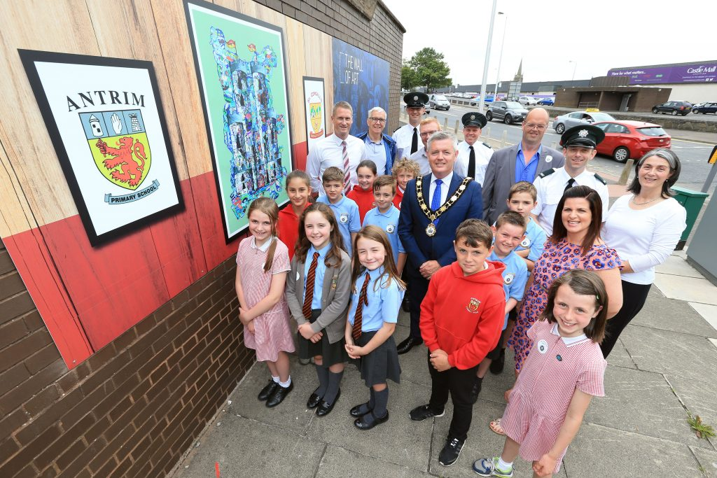 The Mayor, Councillor Paul Michael, unveils the new art installation at Antrim Police Station with local Councillors, PSNI officers, pupils and teachers from Antrim Primary School and St. Comgall's Primary School.