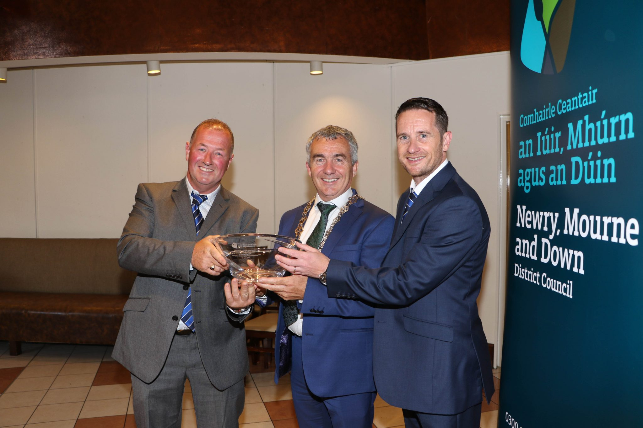 Chairperson Newry City AFC, Martin McLaughlin and Darren Mullen Manager accept an inscribed bowl from Chairperson Newry, Mourne and Down District Council, Councillor Mark Murnin.