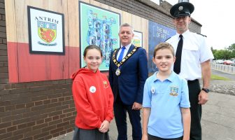 The Mayor, Councillor Paul Michael, unveils the new art installation at Antrim Police Station with Constable Peter Lally, Holly Geddis (Antrim PS) and Matthew Brown (St. Comgall's PS).