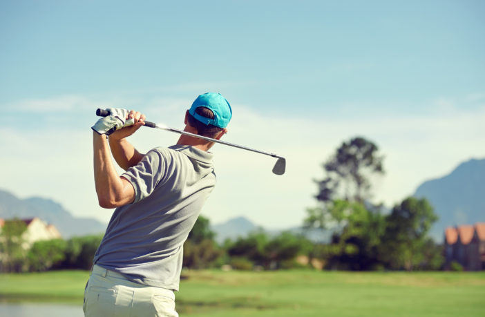 Golfer hitting golf shot with club on course while on golf tour